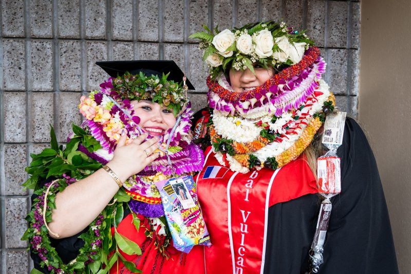 Two women graduates with lei up to their eyes.
