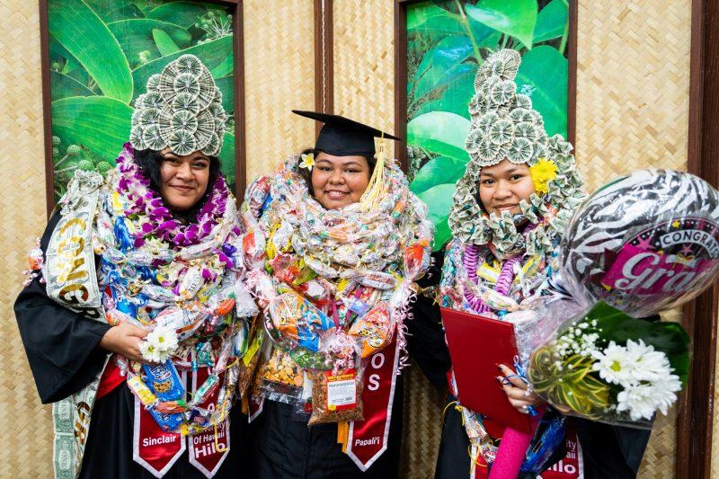 Three women graduates, two with large head dresses.