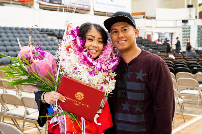 Graduate with lei up to her neck stands with man.