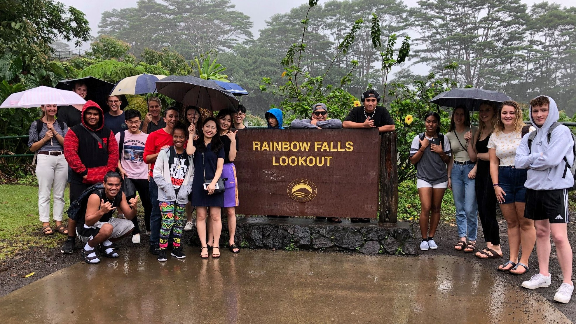 Large group of students stand next to sign for Rainbow Falls.