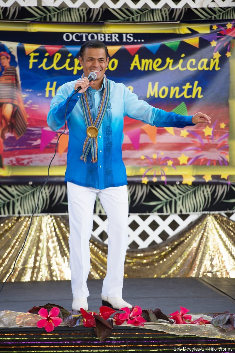 Norman Arancon in traditional Filipino attire, sings on stage.