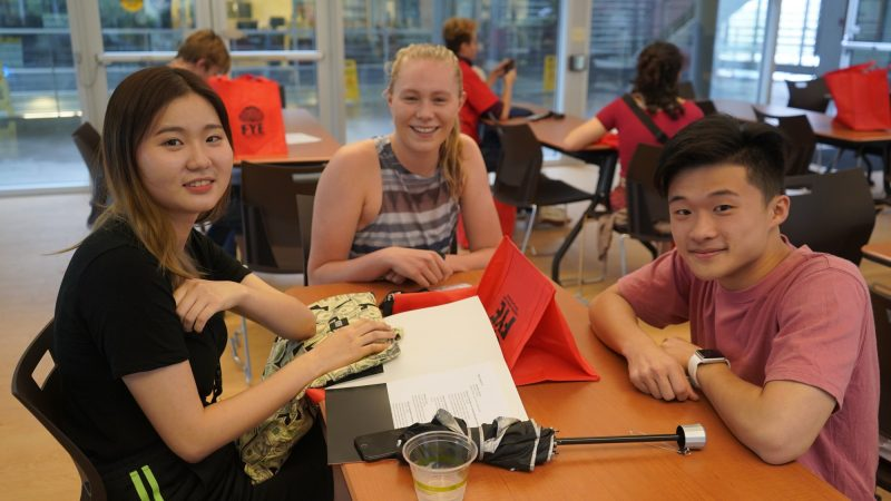 Three students seated at a table with informational materials.