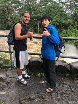 Two young men give the shaka with river in the background.