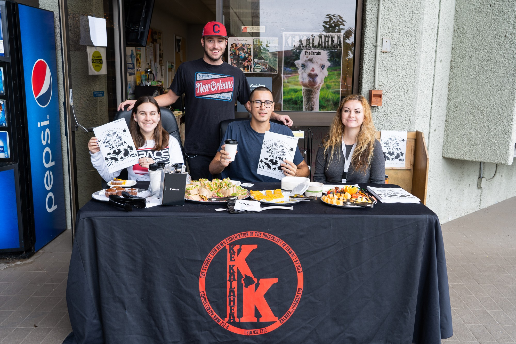 Ke Kalahea staff sit at a table with information leaflets and some food giveaways. The table is covered in a black cloth with Ke Kalahea logo in red.