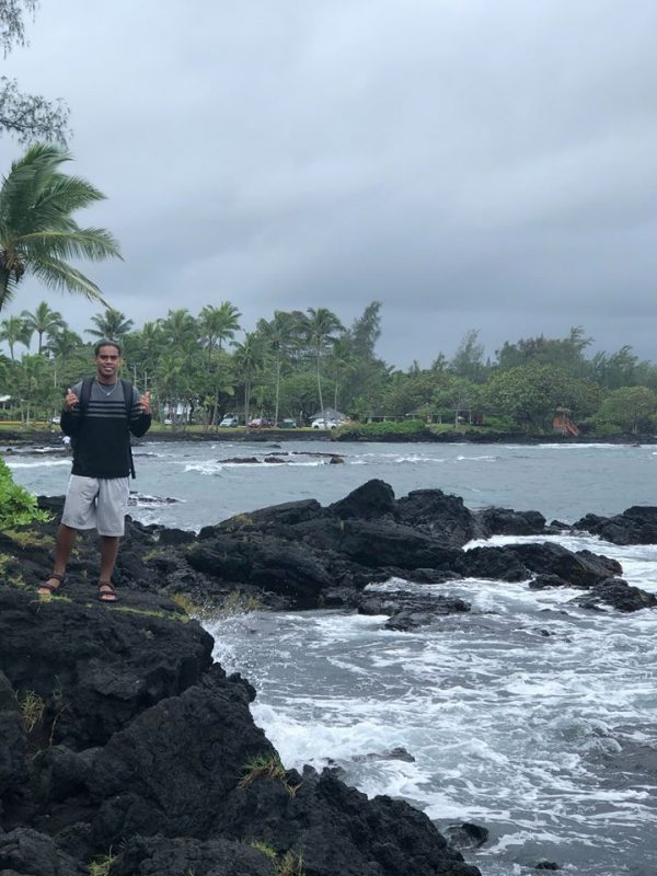 Man stands on rocky ledge at shoreline.