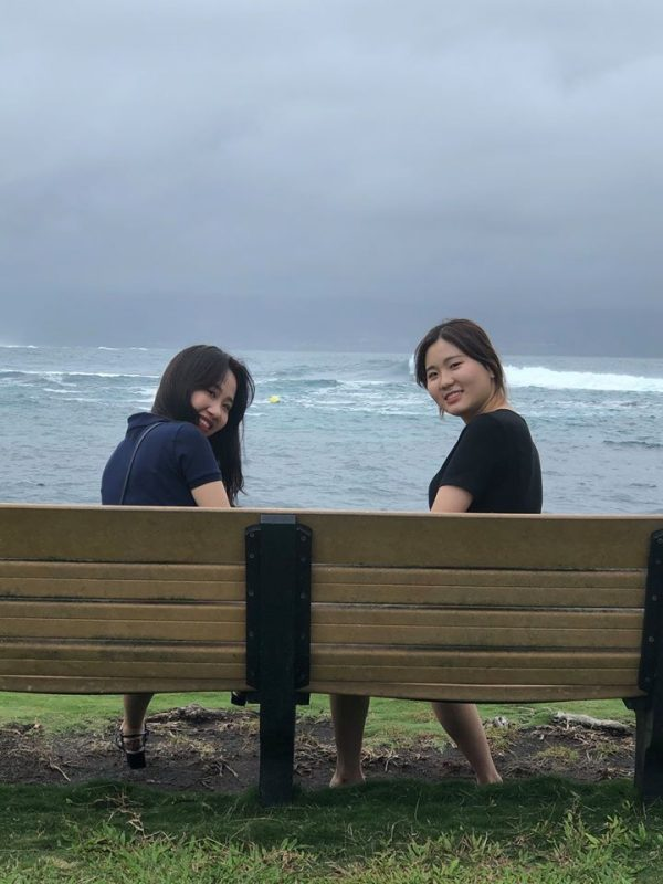 Two women sit on bench at shoreline.