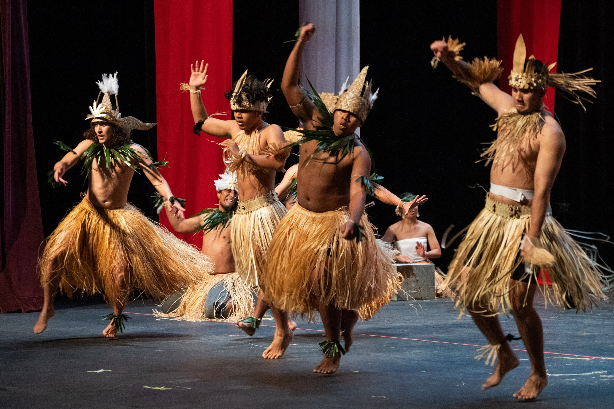 Male dancers in grass skirts and head dresses.