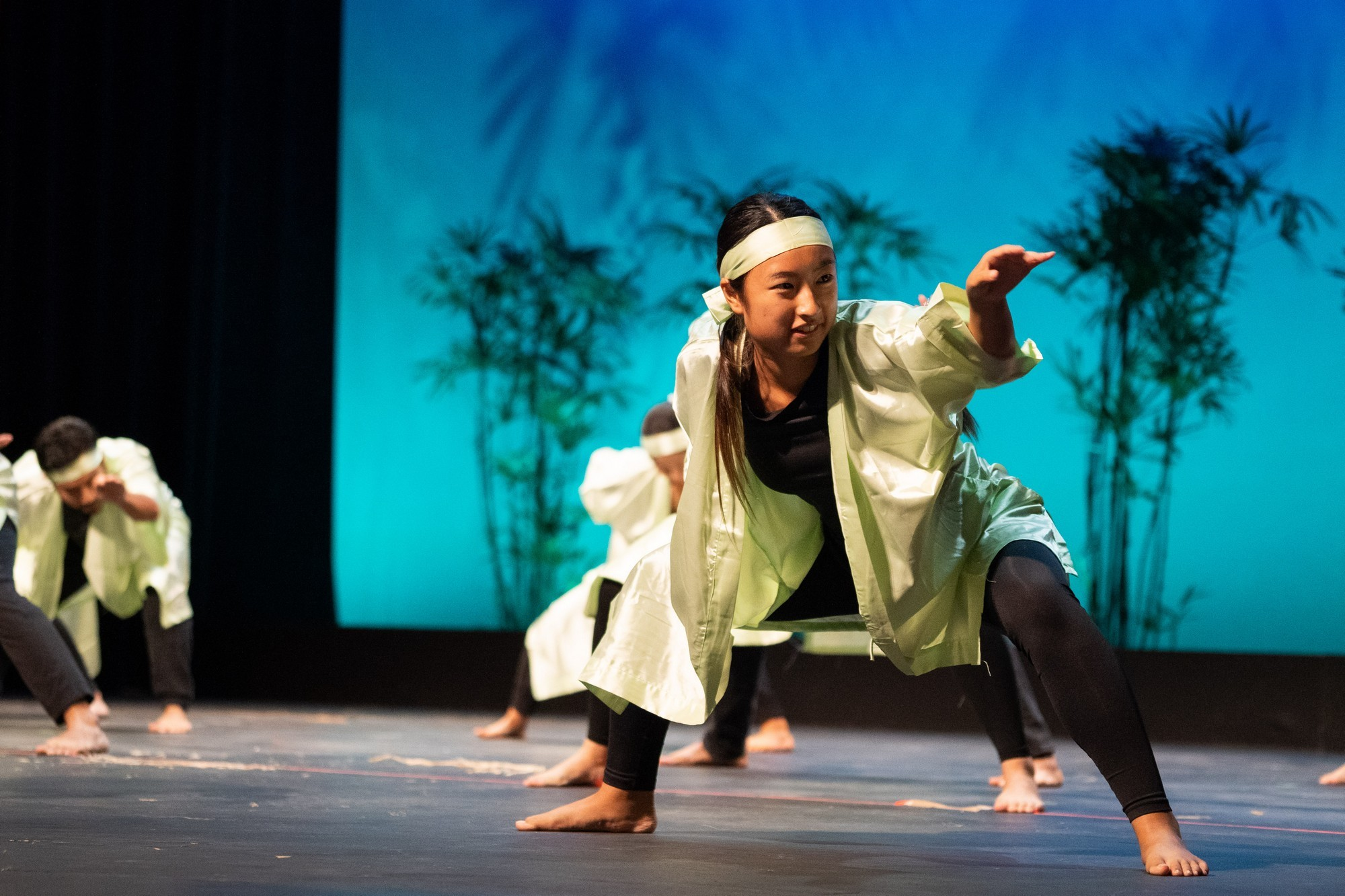 Single female dancer crouching with arm extended.