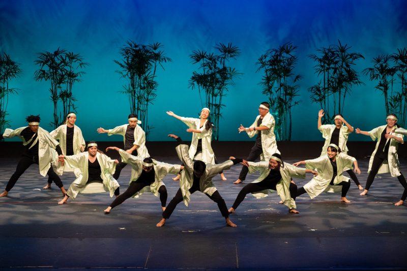 Group of Japanese dancers, white coats, black pants.