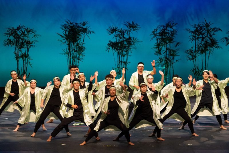Group of dancers wearing balck and white, move in unison.