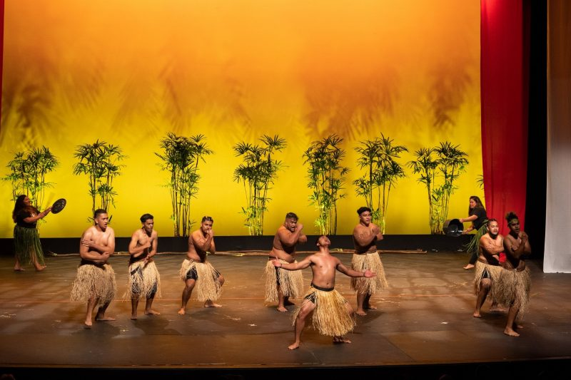 Male dancers in grass skirts, bare tops.