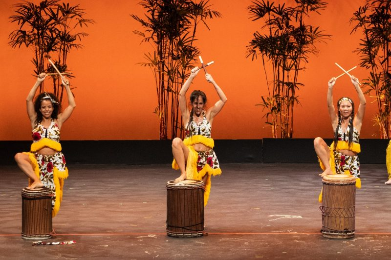 Three female dancers each with one foot up on drum, arms upstretched.