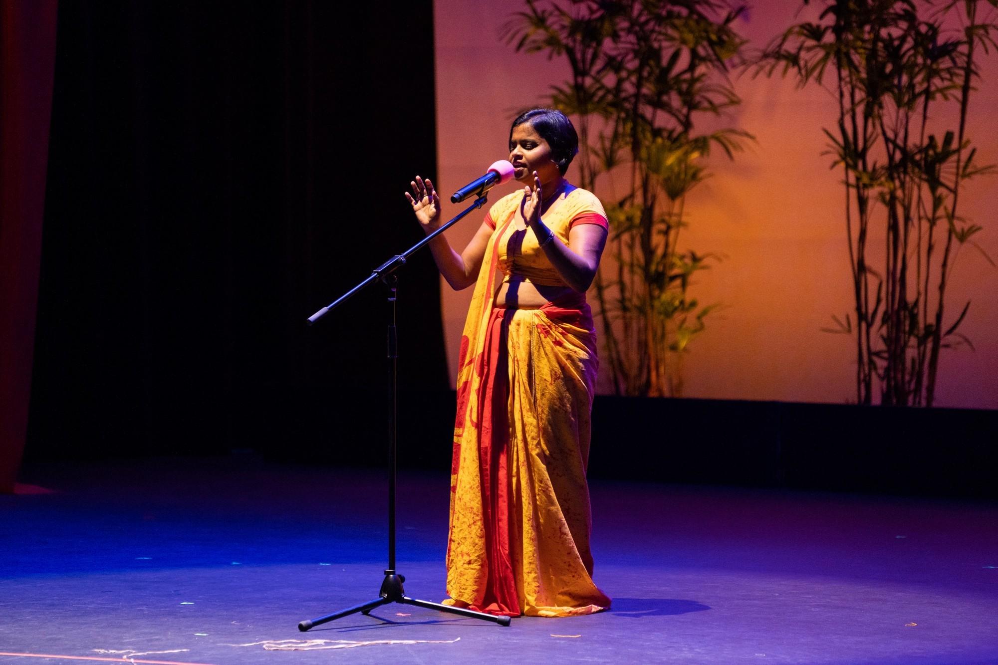 Solo female at mic singing, in orange sari.