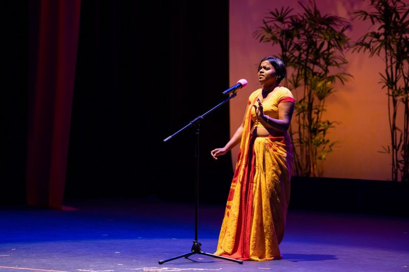 Solo female singing at mic, she is in sari, one hand gestures to her side.