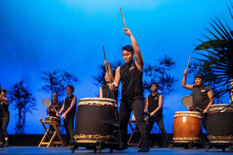 Male Taiko drummer with arm raised high for beat.