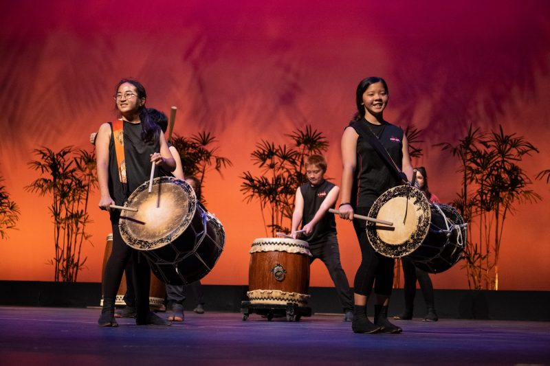 Two female Taiko drummers with each drums and strap over shoulder.