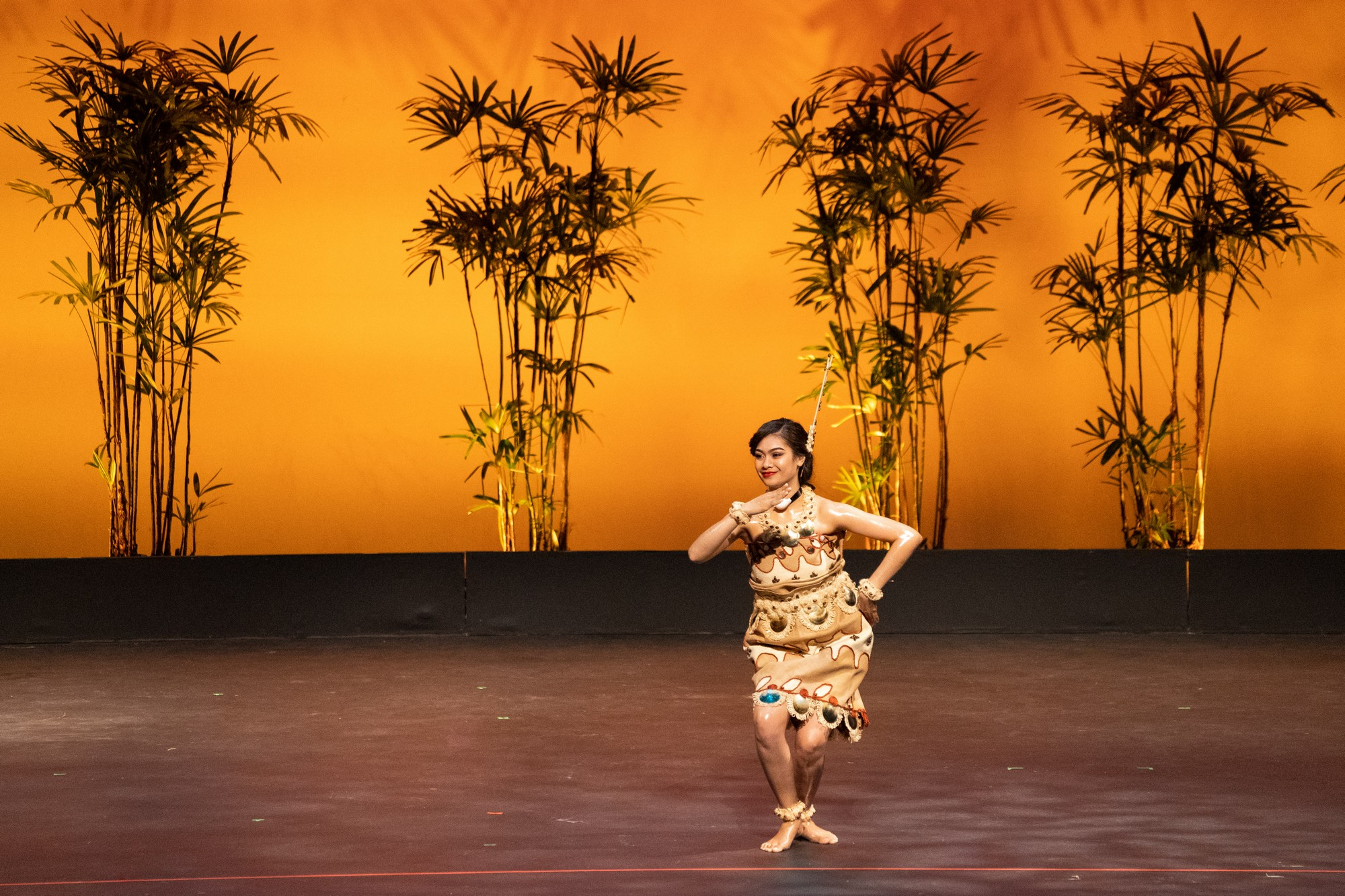 Solo woman dancing on stage, traditional tapa attire.