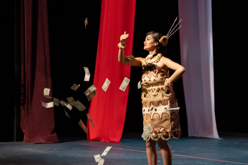 Solo female dancer with money raining down from audience.