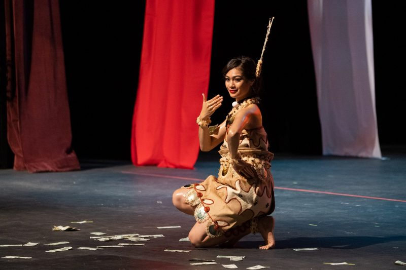 Female dancer kneels down one knee with hand on hip.