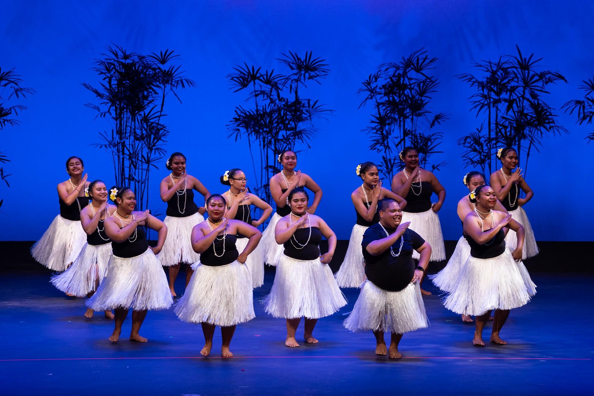 Large group of women dancers in white skirts, black tops, blue lighting.