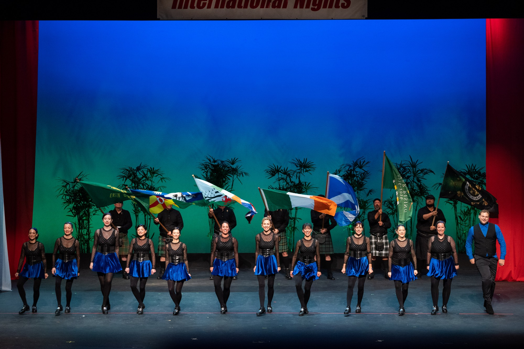 Group of female dancers in line, blue skirts, black tops. In back is line of male dancers holding flags.
