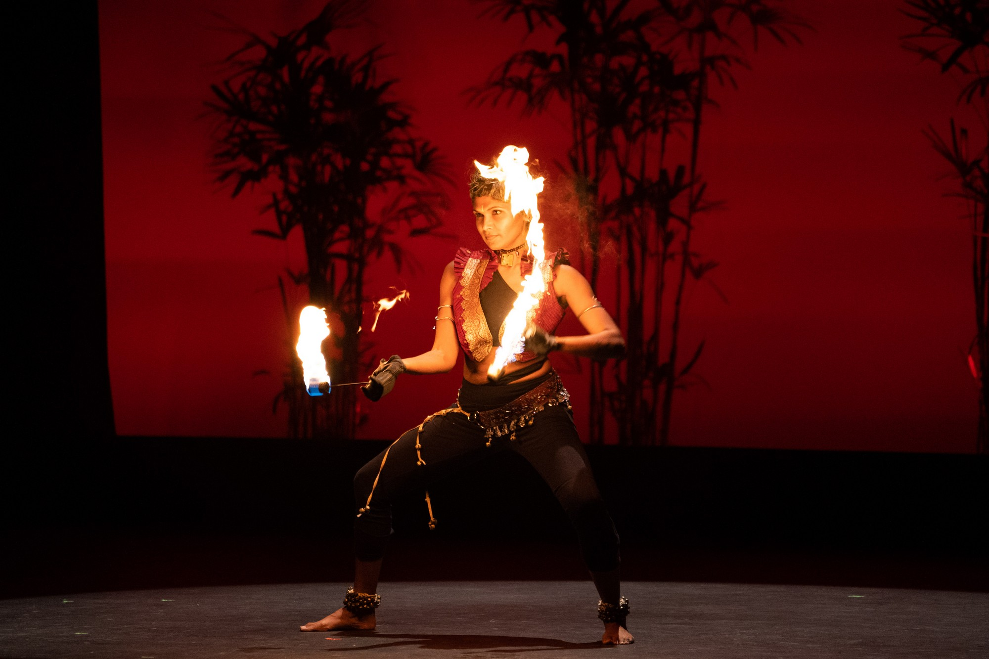 Woman holding fire in each hand.
