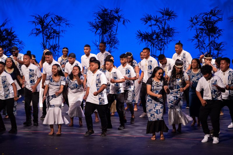 Large group of dancers in dark blue and white dress, men and women.