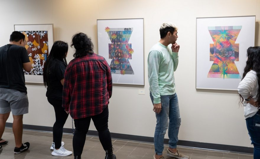 Students looking at hung paintings in exhibit.