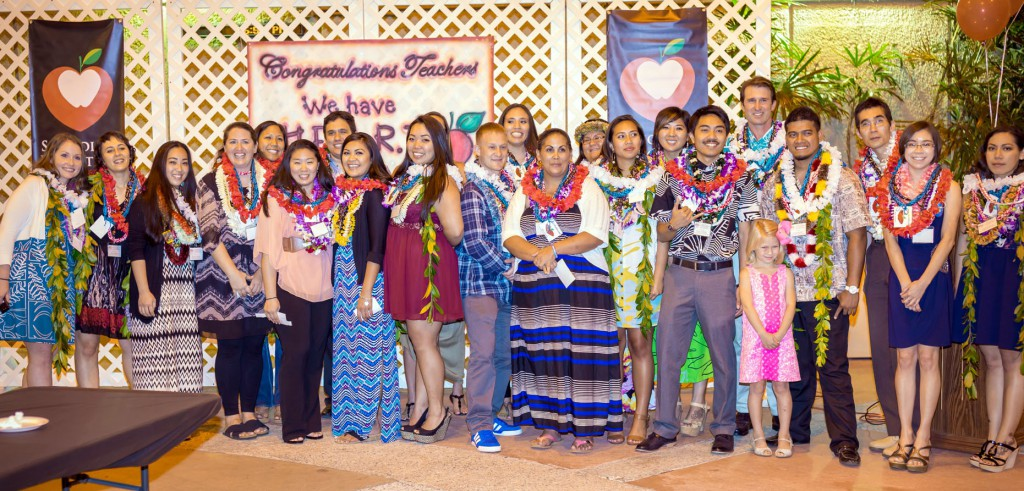 Group of students with lei against backdrop of Congratulations banner and the school logo of apple and heart.
