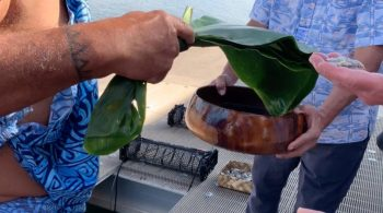 Man holds ti leaf and koa bowl used in blessing ceremonies. IN background is basket of oysters and oyster cage used for containing oysters in the ocean.