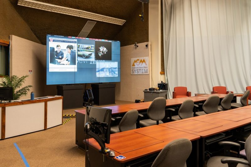Rows of desks facing very large screen with images.