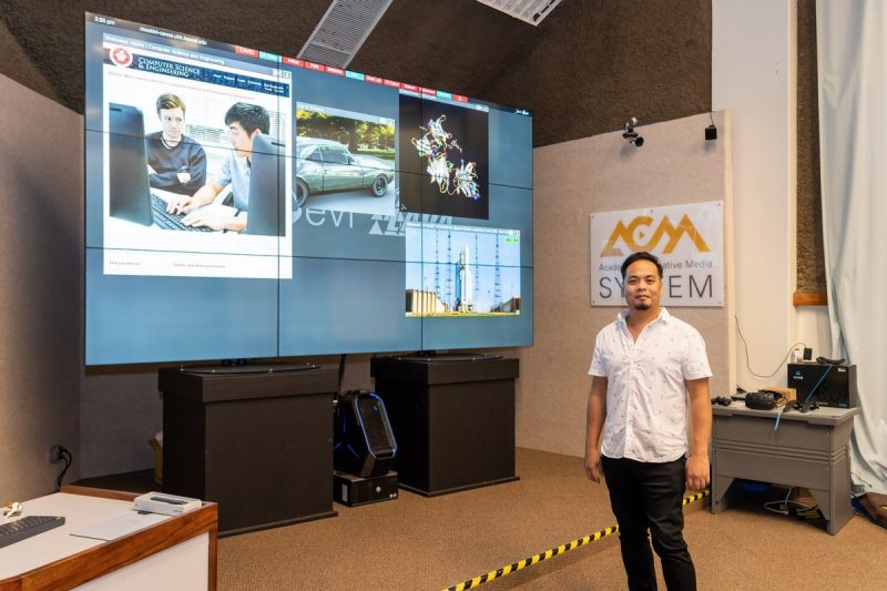 Francis Cristobal stands next to large screen with images.