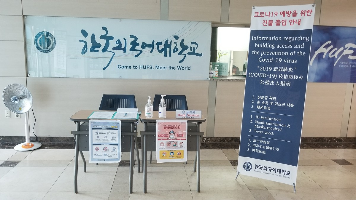 A table set up a lobby with lots of signs directing students to sign in and how to obtain information about Covid-19.