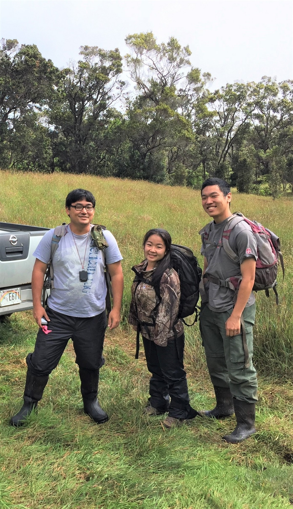 Three researchers (two men, one woman) each with backpack, stand in open field, forest in background.