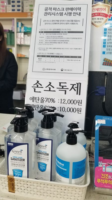 Shop counter with bottles of sanitizer. Signs are in Korean.