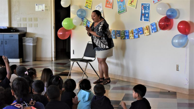 Woman at front of room speaks to schoolchildren.