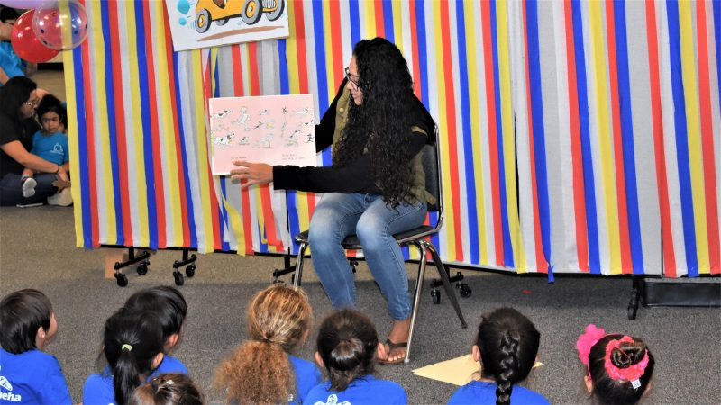 Seated woman holds book to side so children can see pictures.