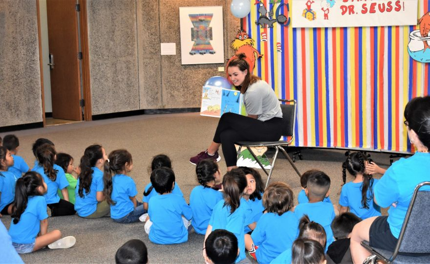 Woman seated in front of group of children, she has book in hand turned so children can see the pictures as she reads.