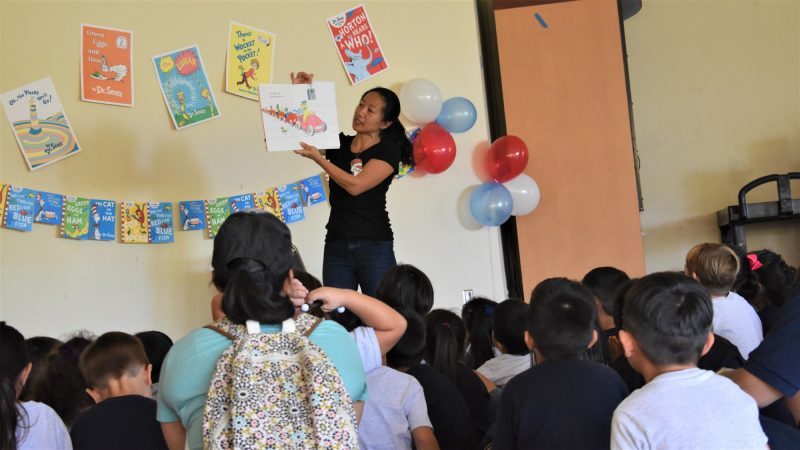 Woman holds up book for children to see pictures.