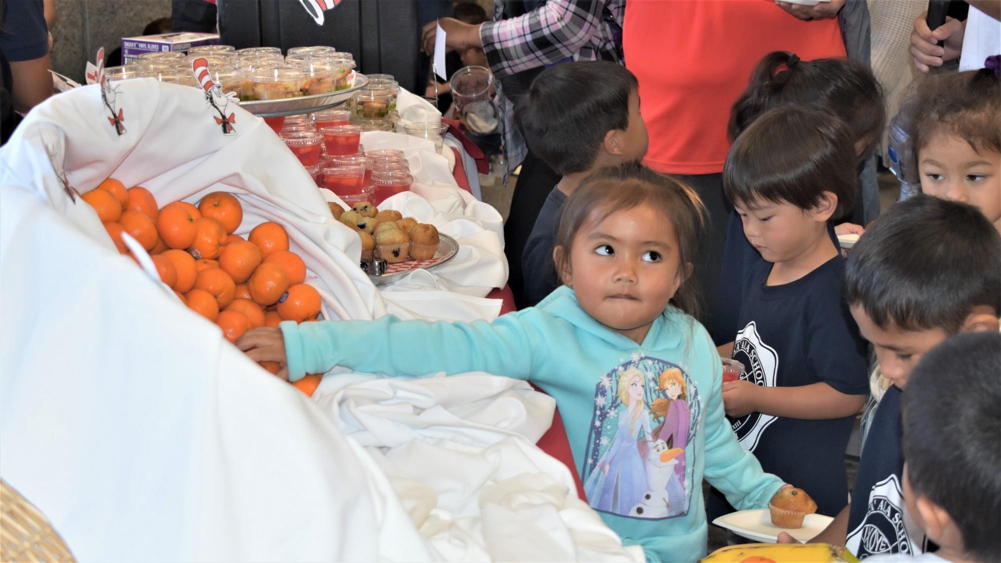 Schoolgirl reaches for orange in basket.