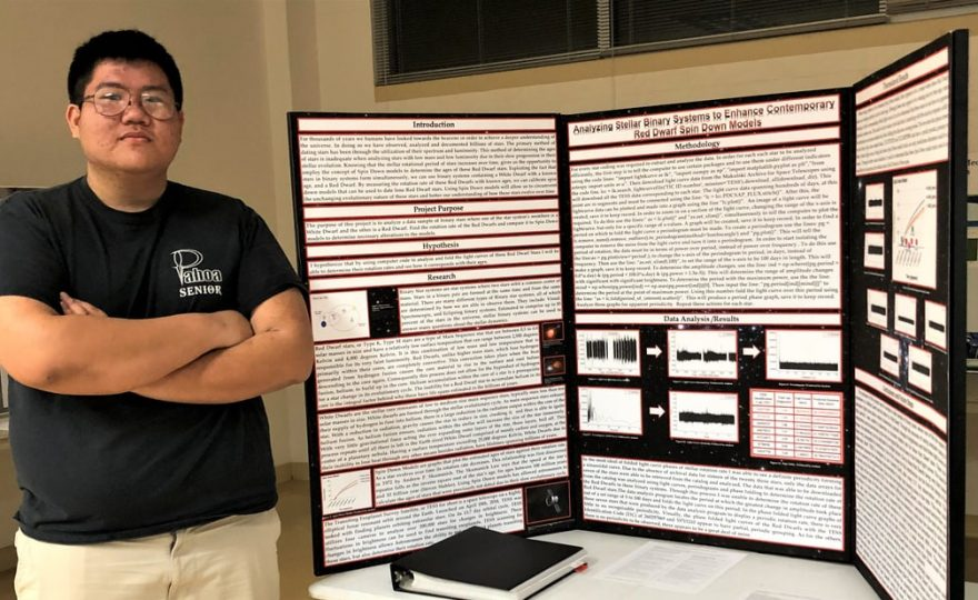 Student in black t-shirt stands next to poster board, which is on a table top.