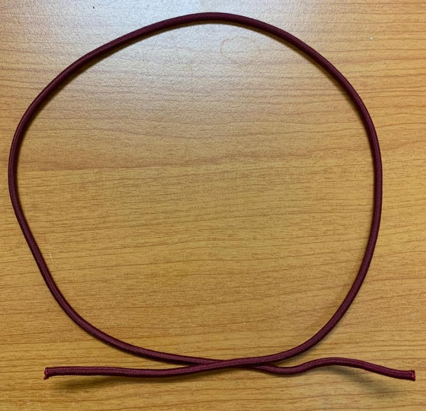 A piece of red elastic cord laid on a table in a circle with overlapping ends.