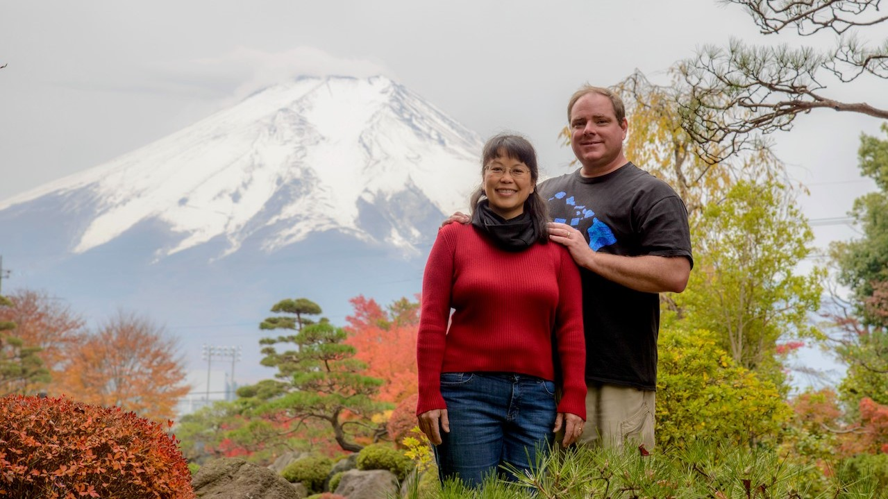 David Phillips and his wife Francine Coloma stand in colorful fall foliage with snowy mountain in background.