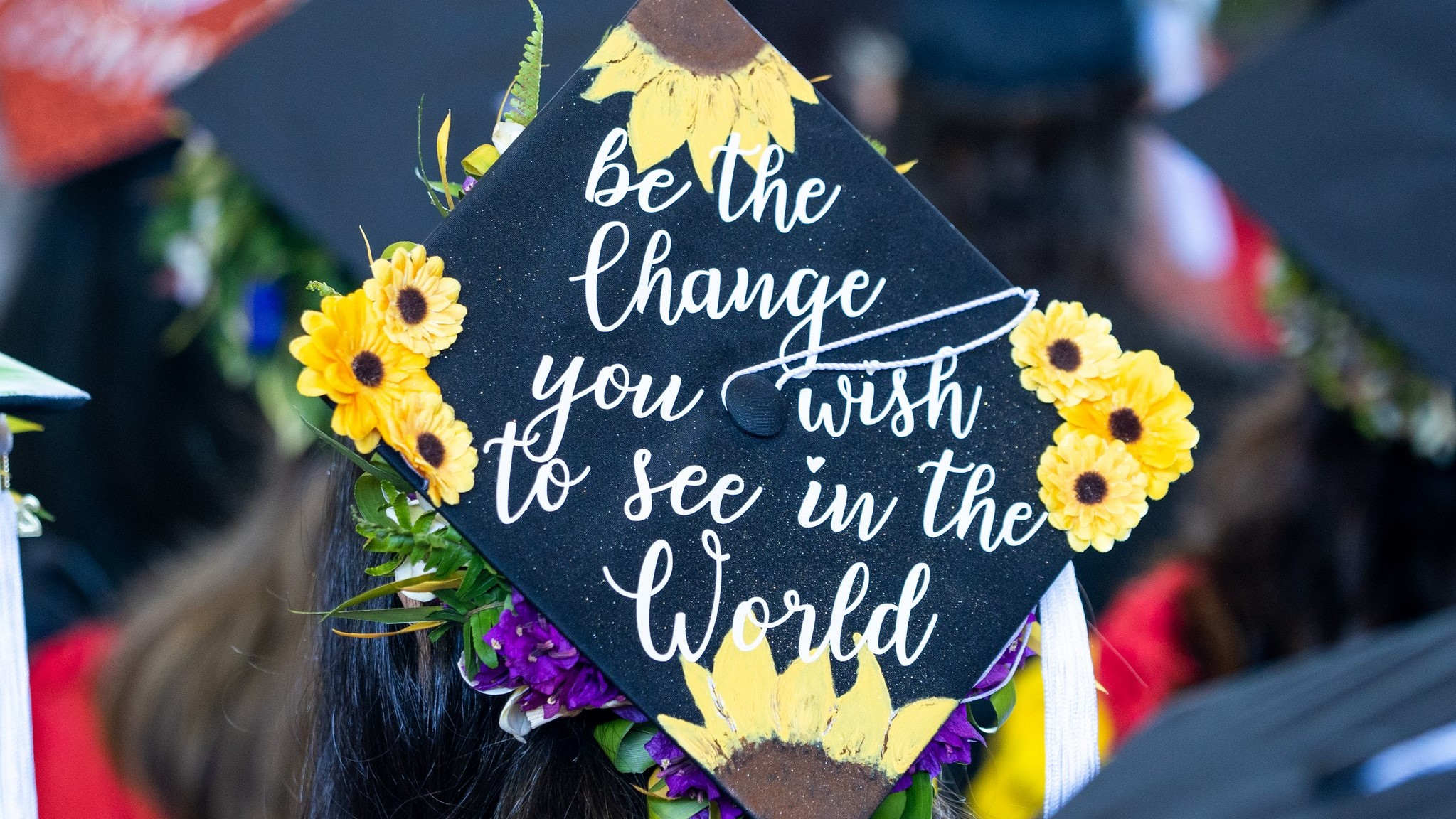 Mortarboard with sunflowers and the words: Be the change you wish to see in the World.