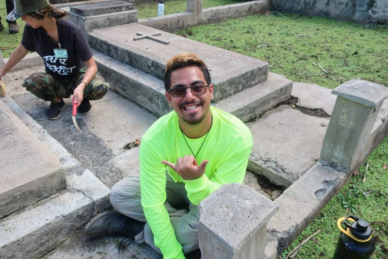 Makoa Caceres flashes the shaka whille seated next to a grave marker.