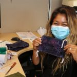 Office worker in mask, holding a cloth mask.