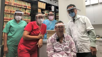 Dentist stands with staff, all wearing the face shields.