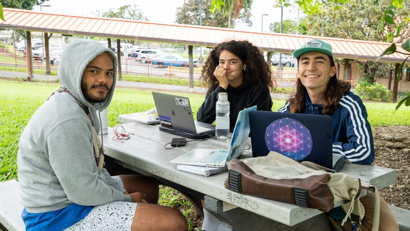 Three students sit at an outside table, two laptops open.
