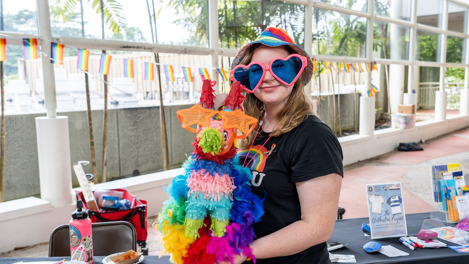 Young woman in huge rainbow colored sun glasses with lenses shaped like hearts. She holds a animal figure made of fringy rainbow colored paper.