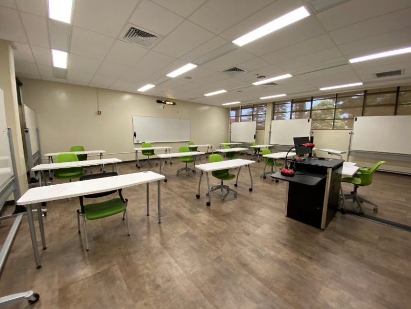 Large desks spaced apart in classroom.